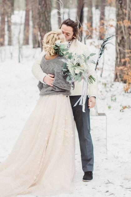Beau couple de jeunes mariés dans la neige avec bouquet de fleurs